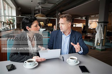 Mature businessman and female colleague with paperwork at cafe table Stock Photo - Premium Royalty-Free, Image code: 698-06615530