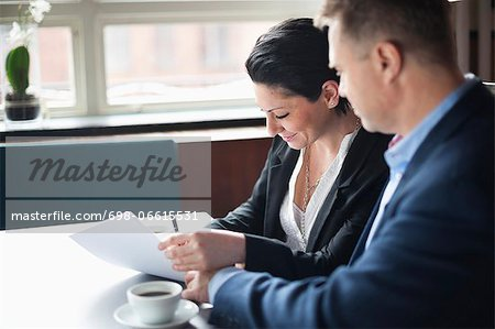 Businessman looking at woman signing contract in cafe Stock Photo - Premium Royalty-Free, Image code: 698-06615531