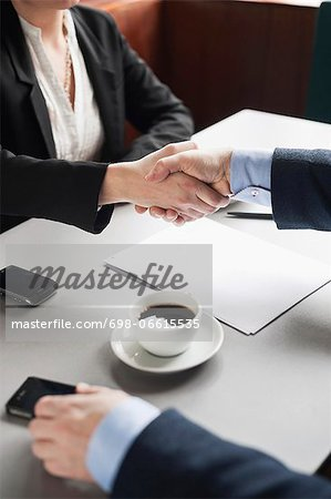 Businesspeople shaking hands over restaurant table Stock Photo - Premium Royalty-Free, Image code: 698-06615535