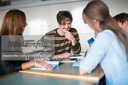 Happy friends with books in classroom Stock Photo - Premium Royalty-Free, Image code: 698-06615563