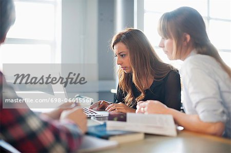 Group of university students using laptop in classroom Stock Photo - Premium Royalty-Free, Image code: 698-06615568