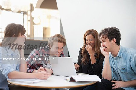 Happy college friends with laptop at restaurant Stock Photo - Premium Royalty-Free, Image code: 698-06615593