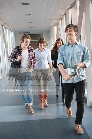 Happy young university student walking in corridor Stock Photo - Premium Royalty-Free, Image code: 698-06615598
