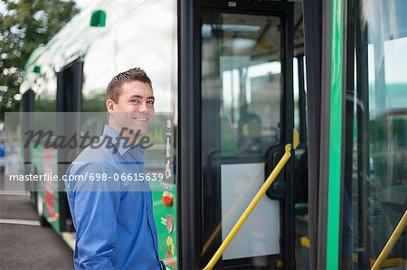 Portrait of happy mid adult man entering bus Stock Photo - Premium Royalty-Free, Image code: 698-06615639