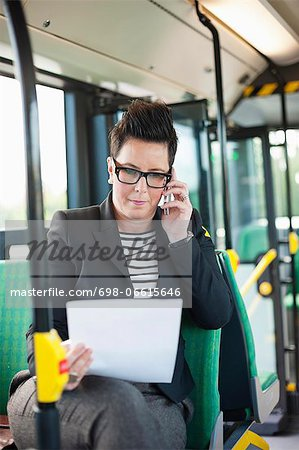 Mid adult businesswoman with document using cell phone in bus Stock Photo - Premium Royalty-Free, Image code: 698-06615646