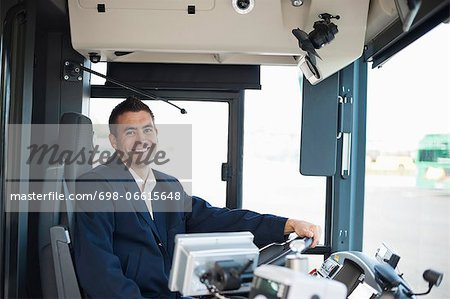 Portrait of happy mid adult bus driver Stock Photo - Premium Royalty-Free, Image code: 698-06615648