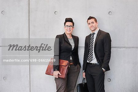 Portrait of happy business people holding bags against wall Stock Photo - Premium Royalty-Free, Image code: 698-06615669