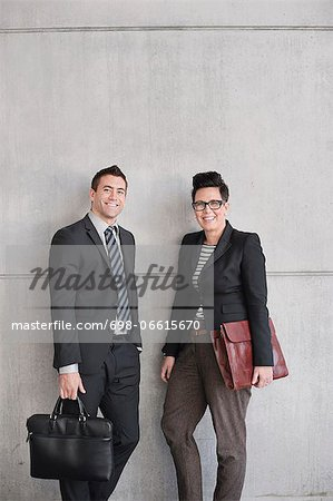 Portrait of happy business people with bags standing against wall Stock Photo - Premium Royalty-Free, Image code: 698-06615670
