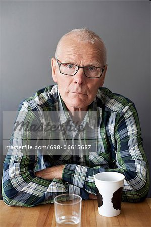 Portrait of senior man at table Stock Photo - Premium Royalty-Free, Image code: 698-06615687