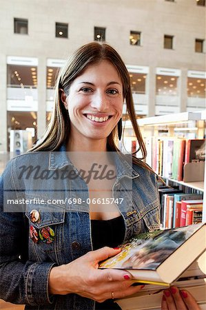 Portrait of woman with stack of books in library Stock Photo - Premium Royalty-Free, Image code: 698-06615747