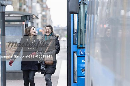 Happy friends in jackets walking by bus Stock Photo - Premium Royalty-Free, Image code: 698-06615845