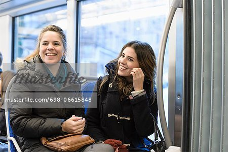 Happy female friends looking away while sitting in bus Stock Photo - Premium Royalty-Free, Image code: 698-06615848