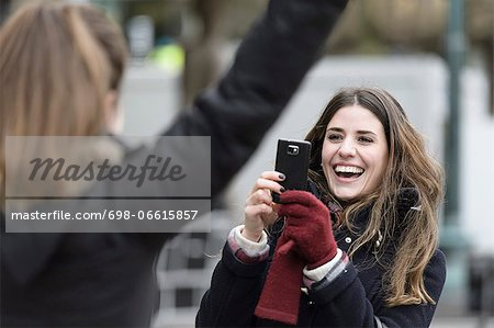 Happy young woman photographing friend through mobile phone Stock Photo - Premium Royalty-Free, Image code: 698-06615857