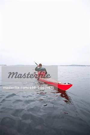 Rear view of mid adult man kayaking in river Stock Photo - Premium Royalty-Free, Image code: 698-06615875