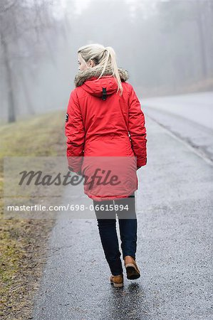 Rear view of young woman in winter coat walking on road Stock Photo - Premium Royalty-Free, Image code: 698-06615894