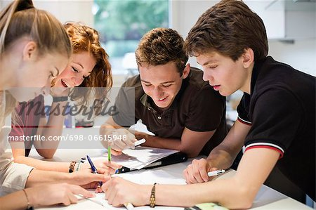 Happy young students studying together at table Stock Photo - Premium Royalty-Free, Image code: 698-06615948