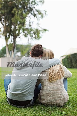 Rear view of young couple with arms around sitting at park Stock Photo - Premium Royalty-Free, Image code: 698-06615976