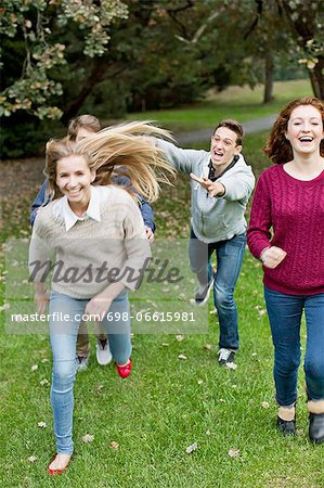 Cheerful young friends playing at park Stock Photo - Premium Royalty-Free, Image code: 698-06615981