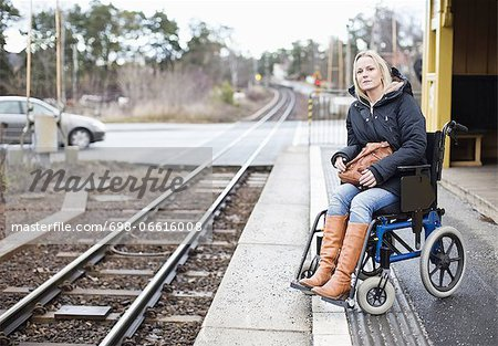 Disabled woman in wheelchair waiting for the train at railway station Stock Photo - Premium Royalty-Free, Image code: 698-06616008
