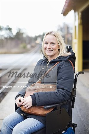 Portrait of happy disabled woman in wheelchair at railway station platform Stock Photo - Premium Royalty-Free, Image code: 698-06616009