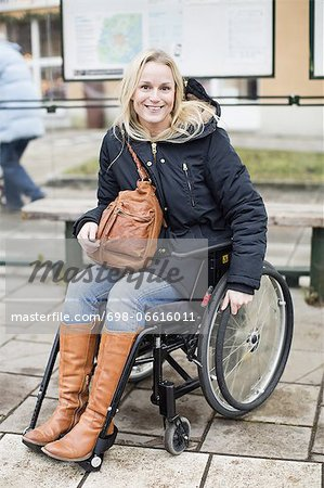 Portrait of happy disabled woman in wheelchair at bus stop Stock Photo - Premium Royalty-Free, Image code: 698-06616011