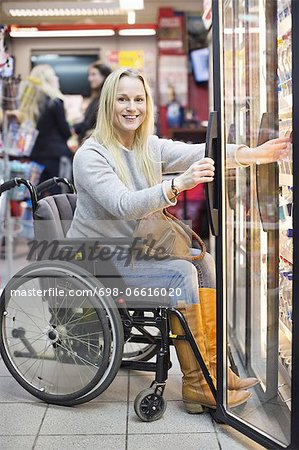 Portrait of happy disabled woman in wheelchair at refrigerated section of supermarket Stock Photo - Premium Royalty-Free, Image code: 698-06616020