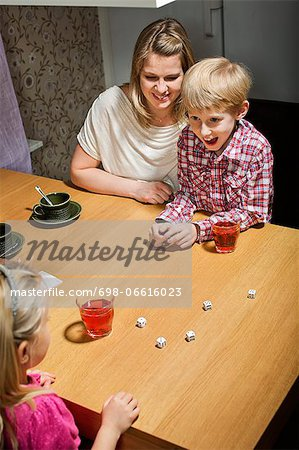 Happy family playing dice game at table Stock Photo - Premium Royalty-Free, Image code: 698-06616023