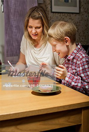 Excited boy playing dice game while mother writing scores at table Stock Photo - Premium Royalty-Free, Image code: 698-06616025