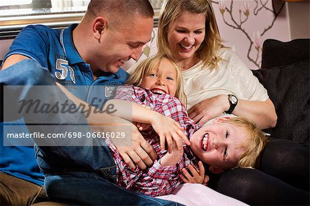 Portrait of mischievous children playing with parents at home Stock Photo - Premium Royalty-Free, Image code: 698-06616029