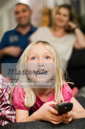 Little girl with remote control watching TV and parents sitting in background Stock Photo - Premium Royalty-Free, Image code: 698-06616033