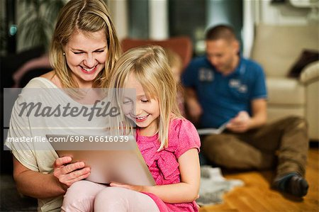 Mother and daughter using digital tablet with family in background Stock Photo - Premium Royalty-Free, Image code: 698-06616039