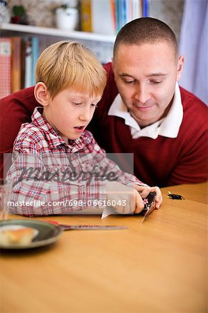 Boy making craft at table while father looking at him Stock Photo - Premium Royalty-Free, Image code: 698-06616043