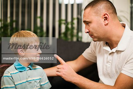 Angry mid adult man disciplining son at home Stock Photo - Premium Royalty-Free, Image code: 698-06616052