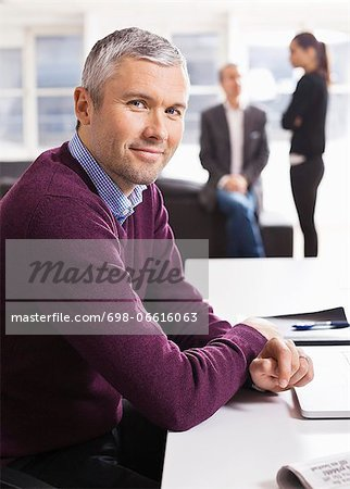 Portrait of businessman smiling at desk with colleagues in the background Stock Photo - Premium Royalty-Free, Image code: 698-06616063