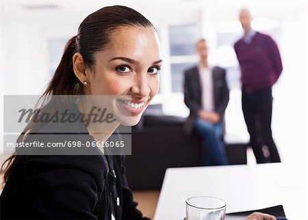 Portrait of happy business woman with colleagues in the background Stock Photo - Premium Royalty-Free, Image code: 698-06616065