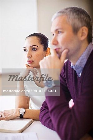 Concentrated business woman with colleague in a meeting Stock Photo - Premium Royalty-Free, Image code: 698-06616081