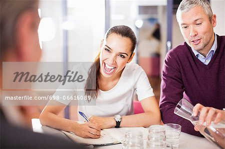 Happy business people in a meeting at desk Stock Photo - Premium Royalty-Free, Image code: 698-06616089