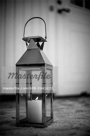 Old-fashioned lantern with lit candle on snow Stock Photo - Premium Royalty-Free, Image code: 698-06616115