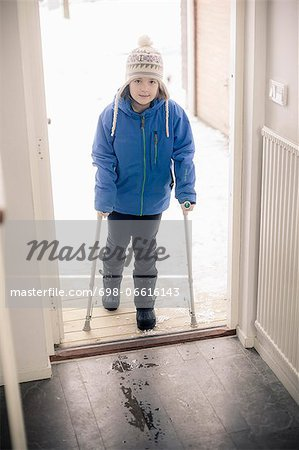 Portrait of disabled girl with crutches entering house Stock Photo - Premium Royalty-Free, Image code: 698-06616143