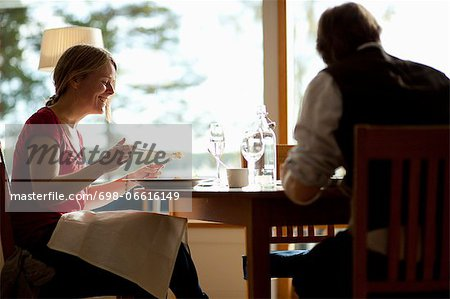 Happy young woman with man having food at restaurant table