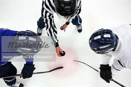 Directly above shot of referee and two ice hockey players in face-off Stock Photo - Premium Royalty-Free, Image code: 698-06616152