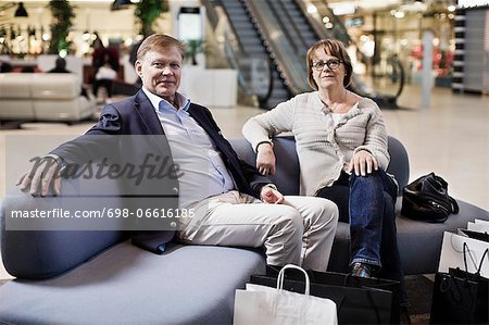 Portrait of senior couple with shopping bags sitting on sofa at mall Stock Photo - Premium Royalty-Free, Image code: 698-06616185