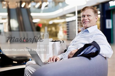 Happy senior man sitting on sofa with laptop at shopping mall Stock Photo - Premium Royalty-Free, Image code: 698-06616191