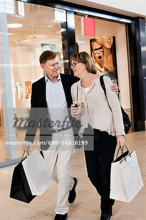 Happy senior couple with shopping bags walking by store in mall Stock Photo - Premium Royalty-Free, Image code: 698-06616199