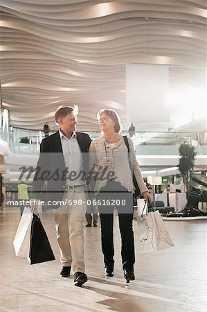Happy senior couple with bags walking in shopping mall Stock Photo - Premium Royalty-Free, Image code: 698-06616200