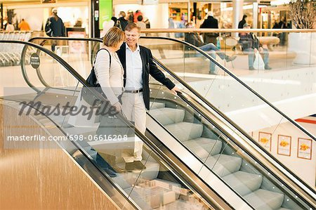 Happy senior couple on an escalator in shopping mall Stock Photo - Premium Royalty-Free, Image code: 698-06616208