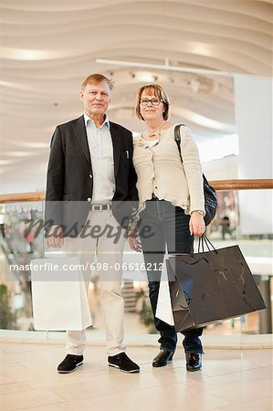 Full length of happy senior couple carrying bags in shopping mall Stock Photo - Premium Royalty-Free, Image code: 698-06616212