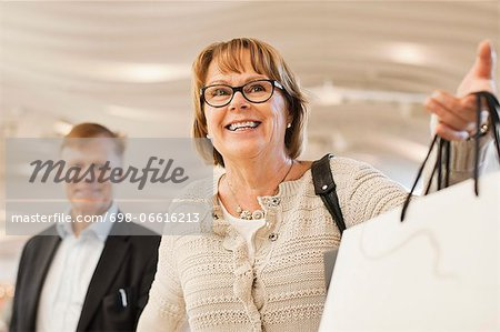 Excited senior woman with man in shopping mall Stock Photo - Premium Royalty-Free, Image code: 698-06616213