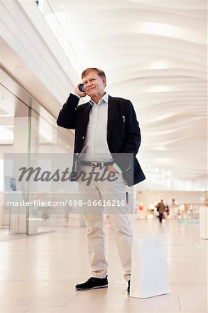 Full length of happy senior man with shopping bag using cell phone in mall Stock Photo - Premium Royalty-Free, Image code: 698-06616216