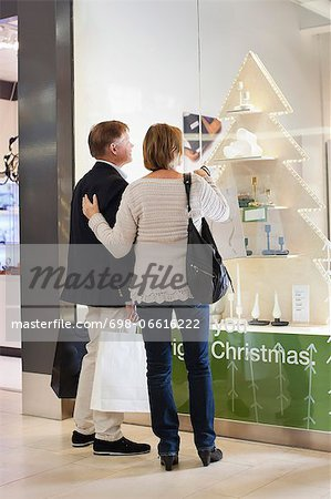 Rear view of senior couple with shopping bags looking in store window Stock Photo - Premium Royalty-Free, Image code: 698-06616222